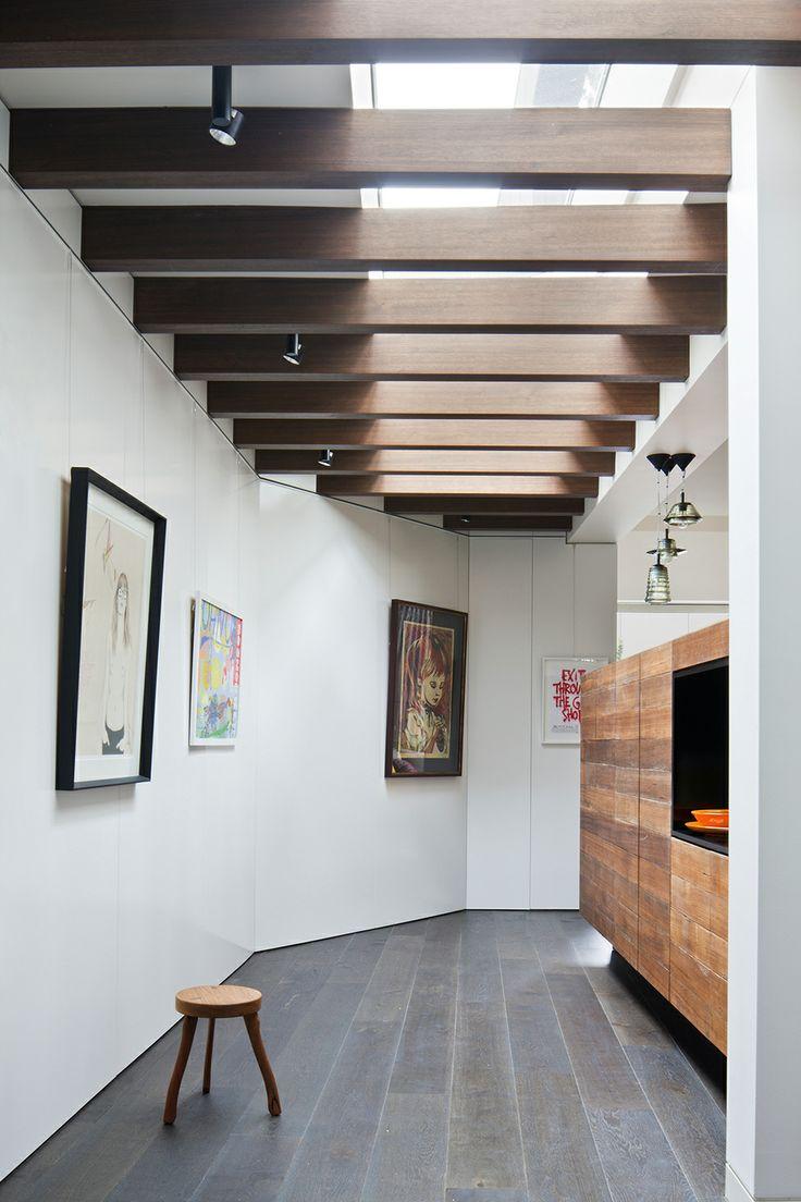 Отделка потолка деревянными брусьями, создает игру света в интерьере.