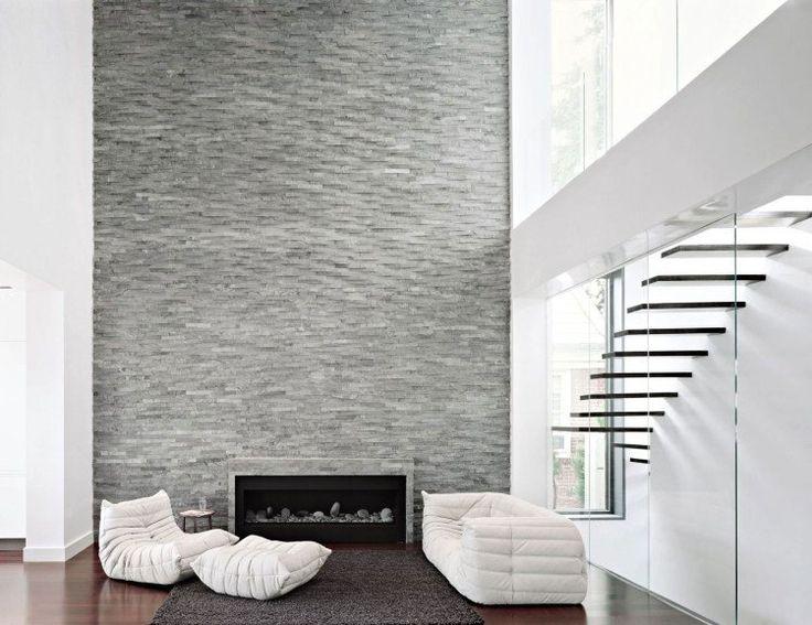 déco salon blanc - habillage de cheminée en tuiles de pierre grise, cheminée à insert moderne, canapé et fauteuil blancs sur un tapis gris