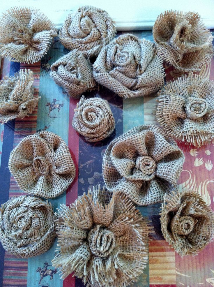 Make an assortment of burlap flowers: some with lace, pearls and dark teal jewels.  To use up scraps from the coffee bean bags.