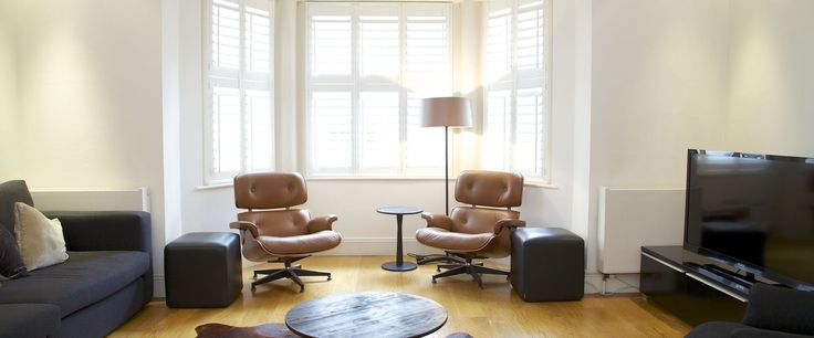 Chic leather sofas and window shutters complement the décor.