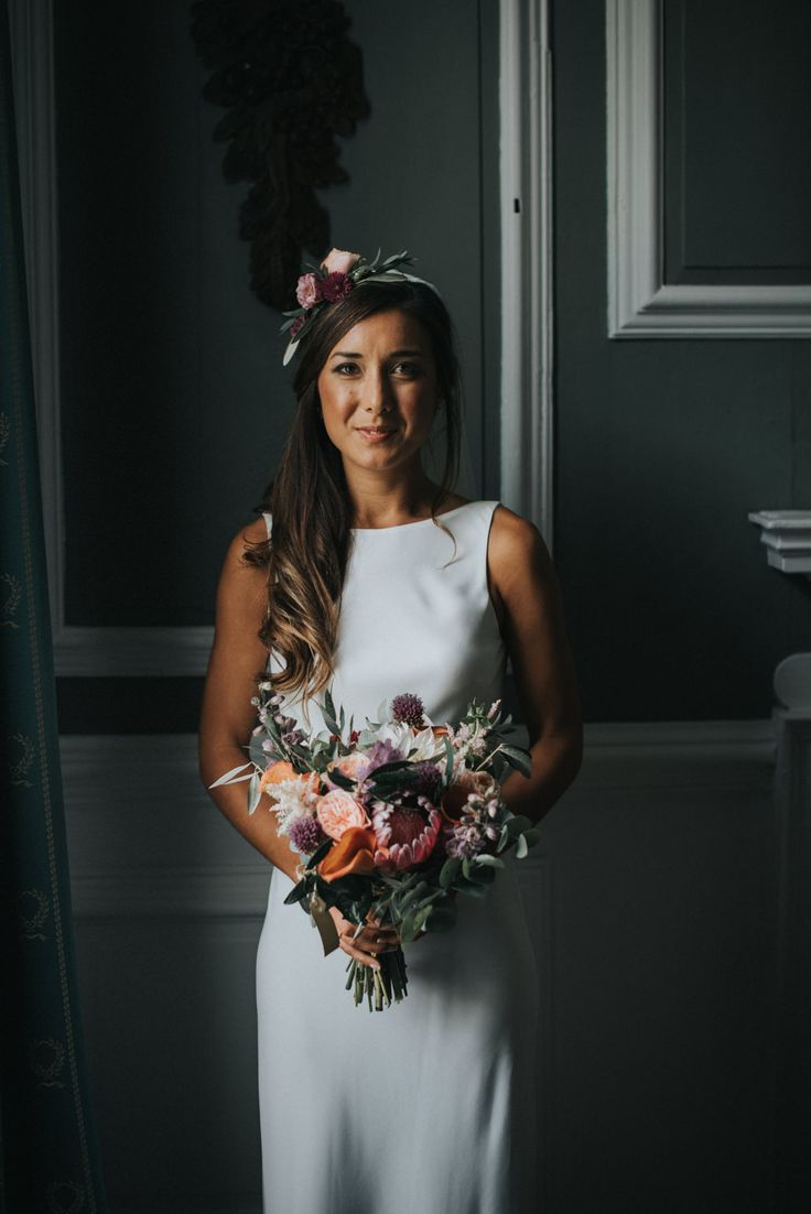 Bride in Charlie Brear Torum Gown with Flower Crown & Bouquet - McGivern Photography | Launcells Barton Country House in Bude Cornwall | Elegant Rustic Barn Wedding | Charlie Brear Torum Gown | Ted Baker Suit | Pink Bridesmaid Dresses