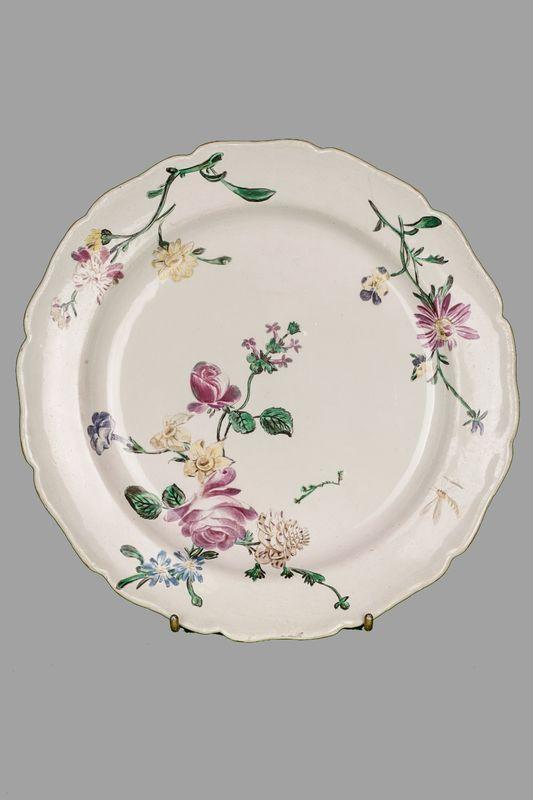 MARSEILLE  Assiette en faïence polychrome à décor floral.  Marque VP au revers sur l'aile.  XVIII ème. Diam: 25 cm