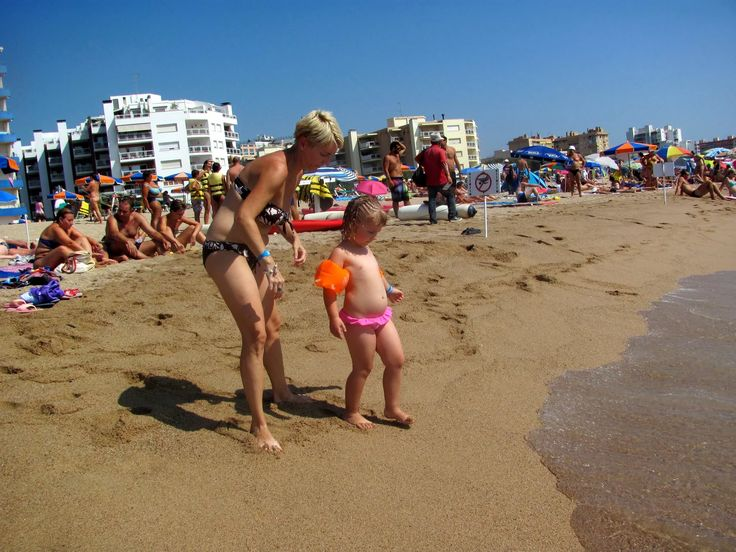 A little girl and her mother play on the sandy beach at the Spanish resort of Santa Susanna near Barcelona. There are many family holiday deals to this European resort.