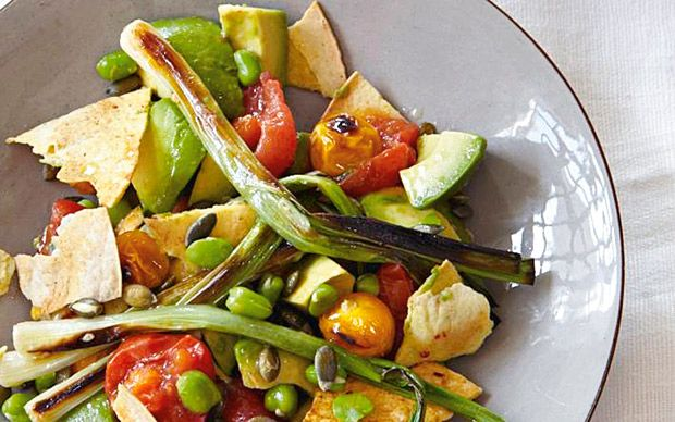 A delicious salad of tomato and avocado with baked tortilla pieces and grilled   cape gooseberries and spring onions