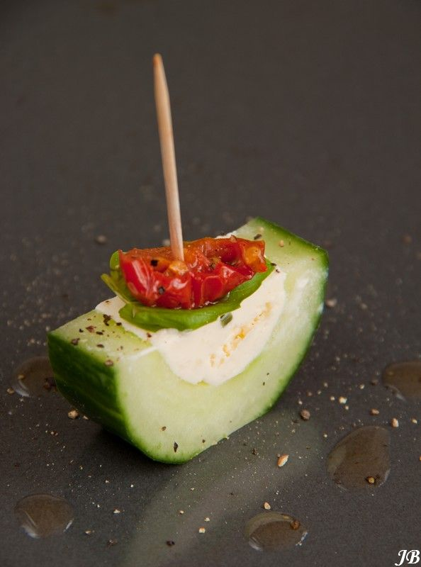 Boursin bite Translated: cream cheese with herbs, cucumber, basil leaf, sun dried tomates, ground pepper.
