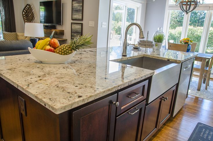 Kitchen island with a stainless steel #farmhouse sink and stainless steel dishwasher. The island comes with cherry cabinets and a granite countertop ©Balducci Additions and Remodeling