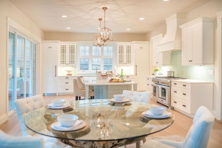 The spacious layout of this kitchen includes room for a glass round table, just right for casual gatherings. Three levels of lighting—recessed ceiling lights, mid-level pendants and task lighting under the cabinets—makes an all-around friendly glow.