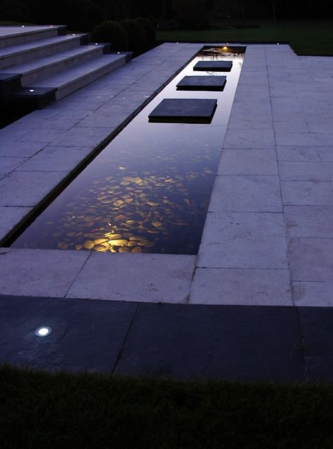 Steps over water feature, limestone pavers, and lighting | David Anderson Landscape Design, UK