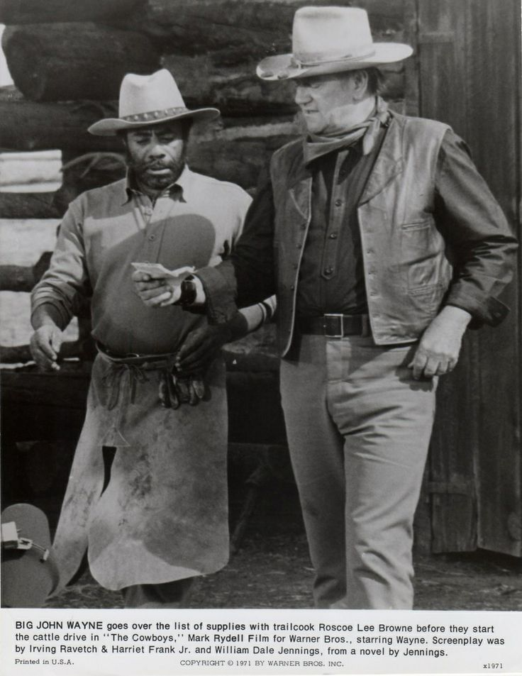 1972 THE COWBOYS / Wil Anderson (John Wayne) goes over the list of supplies with trail cook Jebediah Nightlinger (Roscoe Lee Browne) before they start the cattle drive. (movie trivia - Roscoe Lee Browne was urged by his friends not to work with the right-wing John Wayne. He ignored them and the two actors refrained from discussing politics during filming.)