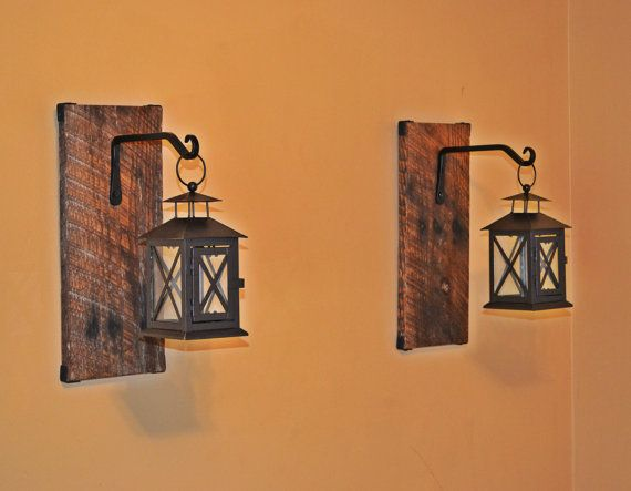 Pair of hanging candle lanterns are hung from black metal hooks complimented by rustic walnut stained reclaimed wood. These unique lanterns feature a door that opens to place your candle inside. Each wood plank has a black corner accent providing a finished look. This lantern set is beautiful addition to your rustic home decor.  Wood panels are 13 long and 5.5 wide. D ring bracket on the back for easy wall hanging. No assembly required.  *Indoor decoration only.  Want something designed and…