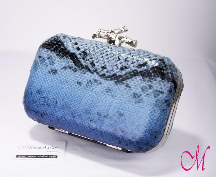 Bolso-clutch en print azul con boquilla metálica plateada acabada en pieza en forma de rama con interior en raso azul. www.monetatelier.com