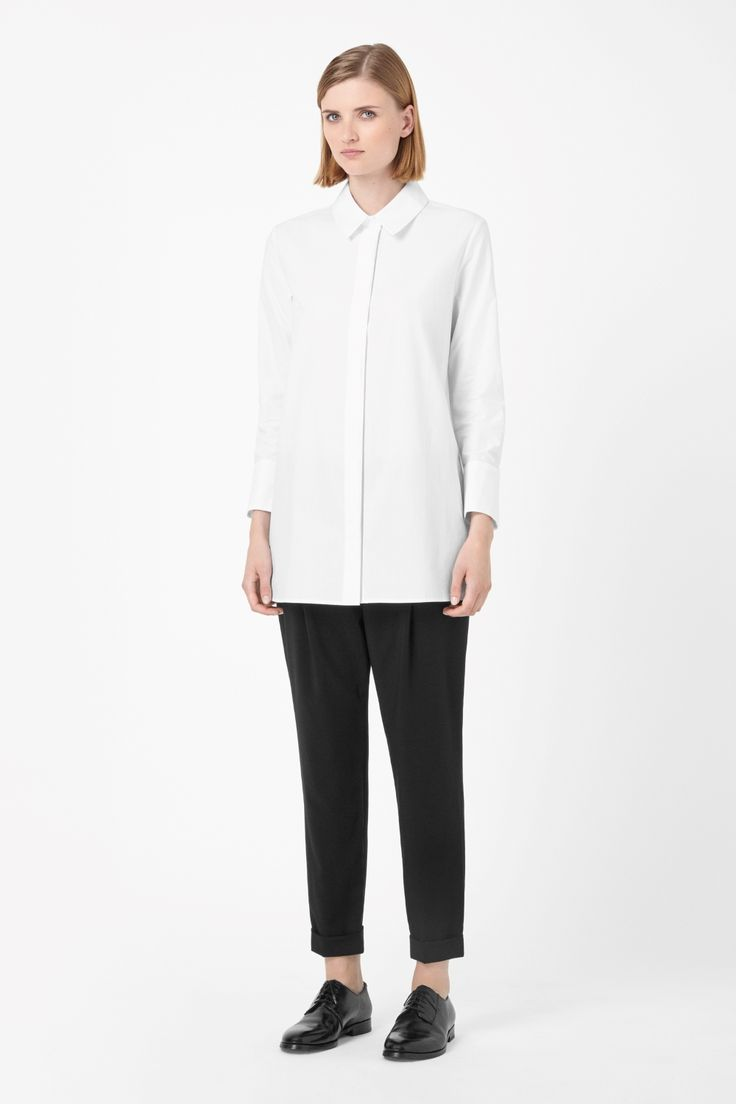 A long style, this straight-cut shirt has a wide pointed collar. Made from crisp cotton poplin, it has long sleeves, oversized cuffs and a hidden button fastening along the front.