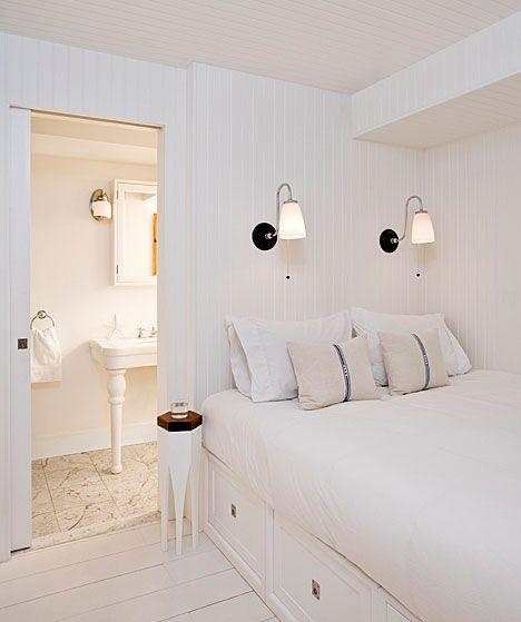 ênfase no branco, cama de casal encostada na parede (ruim pra quem deita do lado da parede?), mesinha ocupando espaço mínimo ao lado da cama, as luminárias são bem legais, gavetas em baixo da cama para aproveitar o espaço