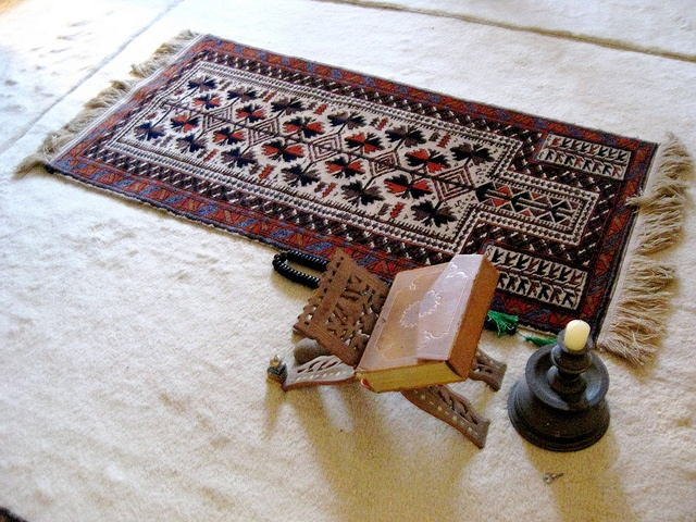 A prayer space in a Muslim house includes a traditional prayer rug, the Qur'an (holy book), and prayer beads. by annemarieangelo, via Flickr