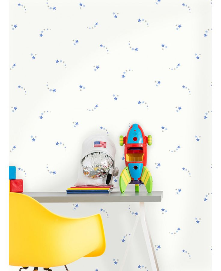 This Shooting Stars Wallpaper features clusters of stars in tones of blue and grey infused with silver glitter on a matte white background. Free UK delivery available