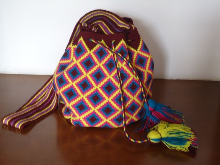 Wayuu Mochila with Paleteado Strap (Medium Size) Certification of the Original QUALITY: handwoven in only one thread. We only sell pieces of art Colors: Pink, Green, purpure, violet We give a Wayuu Bracelet (M) Medium Size with every bag 22 cms aprox x 26 cms aprox Description :Medium size, Wayuu mochila with Paleteado strap , manybright colors and different patterns . Every piece is unique and differentProduction : 100 units every Price:  Euros $63 US$86