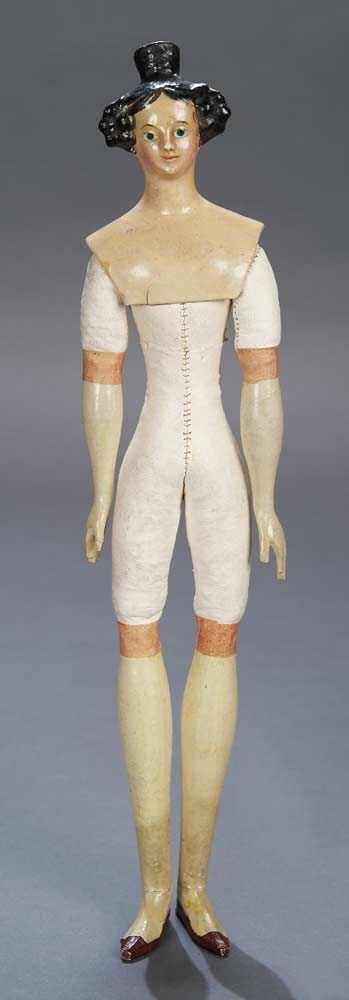 """13"""" German papier-mâché """"milliner's model"""" doll with Apollo knot hairstyle, slender kid body with wooden lower arms and legs, original paper bands at kid/wood junctions. Circa 1840."""