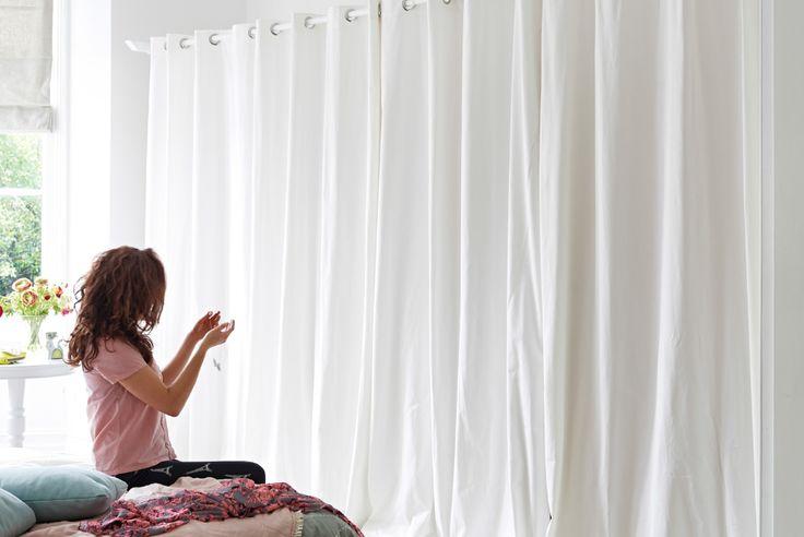 Ein Schlafzimmer, eingerichtet u. a. mit MERETE Gardinenpaar in Beige, die vor einem Kleiderschranksystem hängen.