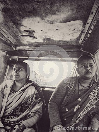 Two North Indian Women ride in a rustic motor rickshaw wearing traditional clothing. This is a black and white vintage style image.