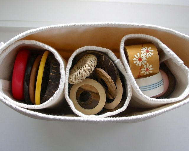 storage cylinders filled with bangles, wooden rings and serviette rings. 3 cylinders fit in a rectangular shelf storage bag