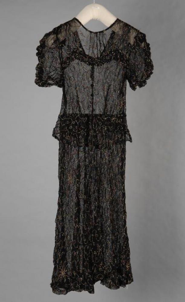 Zwarte kanten jurk van grofgeweven tule-achtige stof met opgenaaide motieven in geel en rood garen, pofmouwen met ruches, bij de taille een ruche-rand | Modemuze