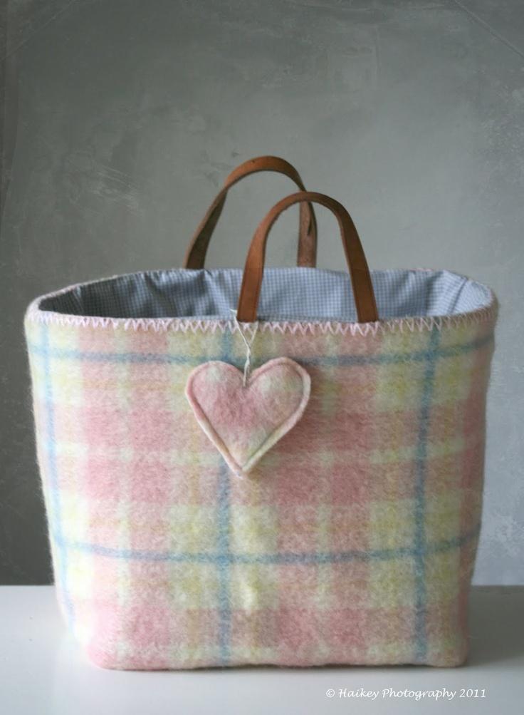 tas-mand van oede deken met leren handvatten ook lek als kranten-of tijdschriften-mand