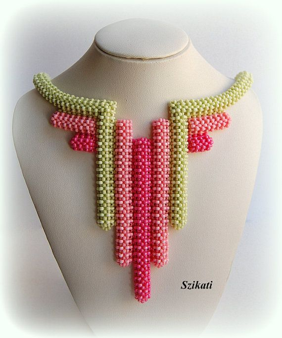 Attractive one-of-a-kind beaded bib necklace with an absolute unique, eye-catching shape and design.  Wonderful combination of coral seed beads and green seed beads.  Length of the strap around the neck: 17 inches / 42,5 cm Length of the focal element: 5 inches / 12,5 cm Closure: magnetic clasp Technique: 3D Right Angle Weave (3D RAW)  Materials: - two shades of coral Czech seed beads - green Czech seed beads  The necklace is my own original design!  This handcrafted piece of fashion jewelry…