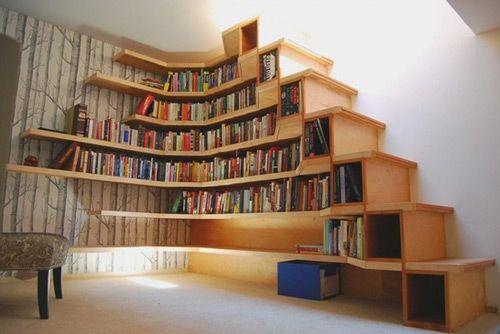 Уголок для чтения с книжными полками вмонтированными в пространство под лестницей