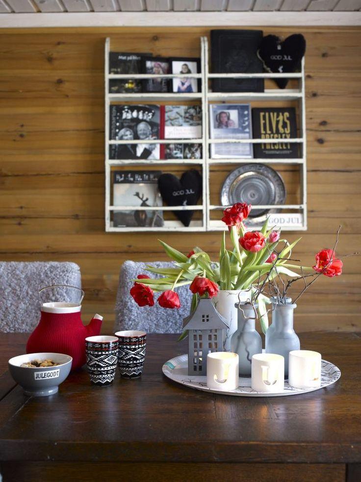 NY VRI: I den hvite tallerkenhyllen over spisebordet har hytteeierne plassert kokebøker. De kjøpte hyllen med tanke på nettopp å oppbevare bøker og bilder. De røde tulipanene er som er spredd rundt i interiøret er viktige for Monica i julen.