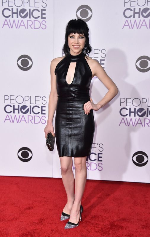 Carly Rae Jepsen con un 'little black dress' de cuero, salones glitter y clutch con detalles brillantes.
