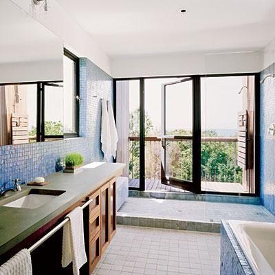 Floor to ceiling iridescent glass tiles make this coastal bathroom feel more like a spa. Coastalliving.com