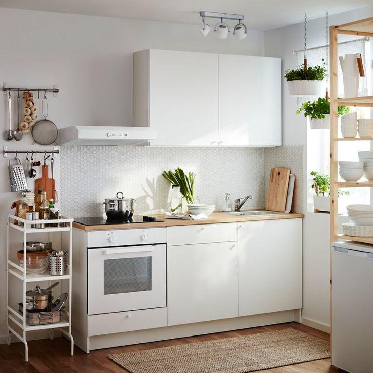 Eine kleine weiße Küche, u. a. mit KNOXHULT Unterschrank mit Türen und Schublade in Weiß und einem Wandschrank in Weiß kombiniert mit einer Dunstabzugshaube, einem Backofen und einem Glaskeramikkochfeld