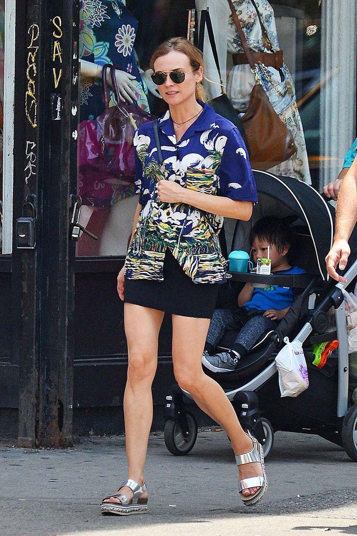 Diane Kruger camisa hawaiiana estampada, minifalda negra, sandalias plateadas con plataforma, bolso bandolera y gafas de sol de aviador