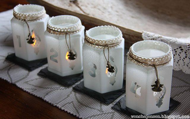 Med et lag frosting på gjenbruksglassene får de et delikat utseende. Tallene og ornamentene lages ved hjelp av klebefolie og en stansemaskin, og dras av når frostingen er tørr. På denne måten blir det et blankt felt som lar lyset skinne gjennom. Lekkert, ikke sant?