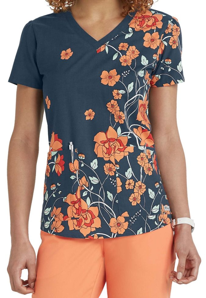 The exquisite Sweet Nouveau print scrub top from the popular Grey's Anatomy collection is perfect for the season! In addition to the vibrant floral print, this top includes two roomy pockets to hold your accessories plus a shirred back yoke and side slits to complete the look.