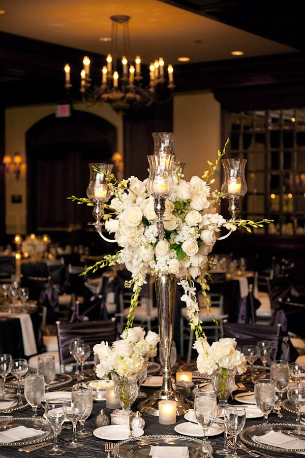 Beautiful reception table setting - large silver candelabra with ivory candles and white and green floral arrangement as centerpiece, silver dishes, and dark purple tablecloth and chair covers - photo by Houston based wedding photographer Adam Nyholt