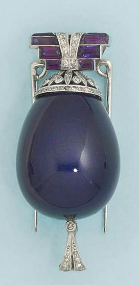 An Art deco amethyst and diamond brooch/pendant  Dual use: the brooch with a geometric surmount of faceted amethyst and millegrain-set diamond detail, to a large polished amethyst drop with similarly-set diamond cap; as a pendant with similarly-set diamond surmount loop, converted from a pendant, circa 1925