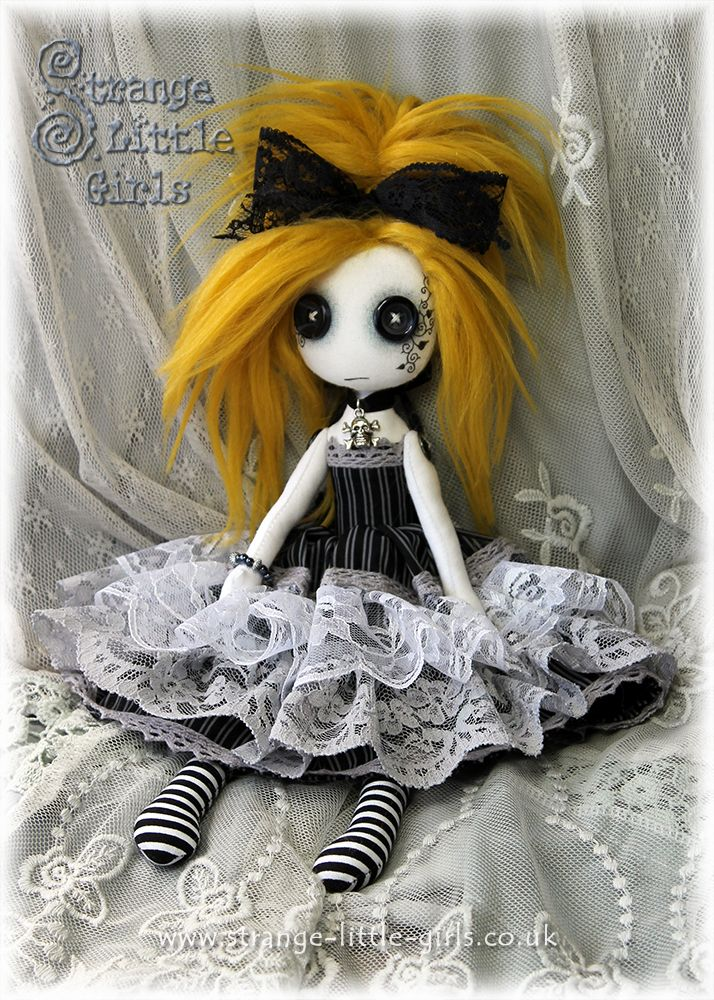 A 10 inch Gothic Lolita doll with button eyes and mustard yellow hair.