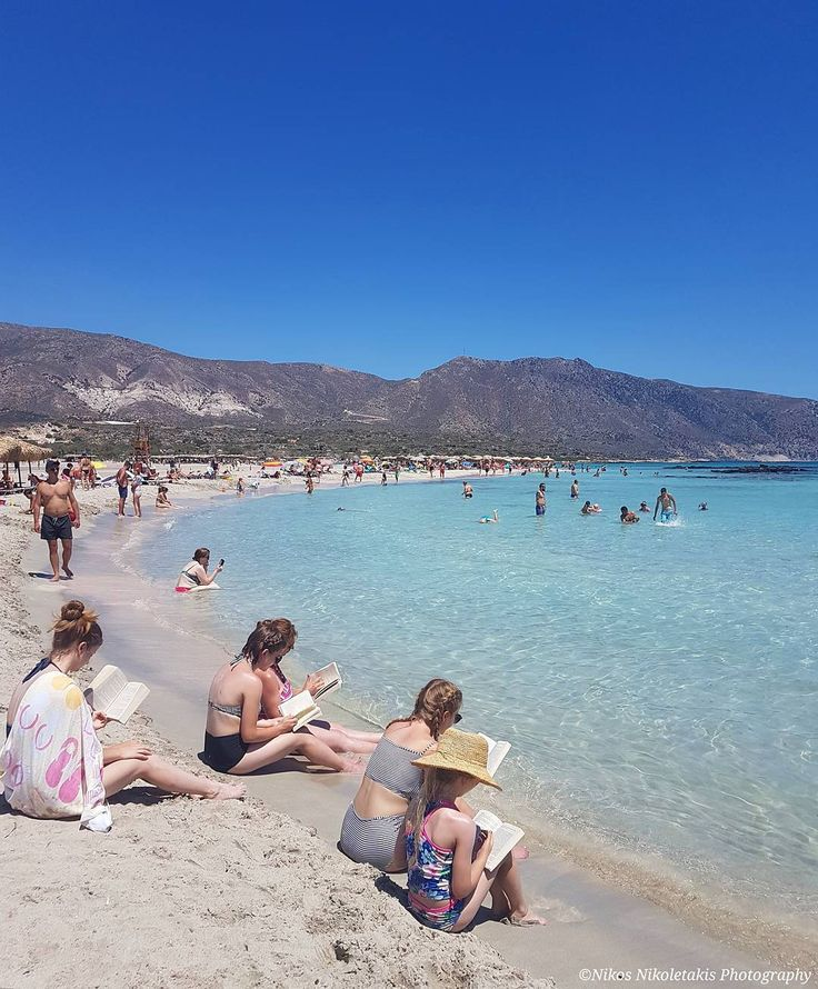Elafonisi island: A hole family reading books at the beach. Happy Sunday!