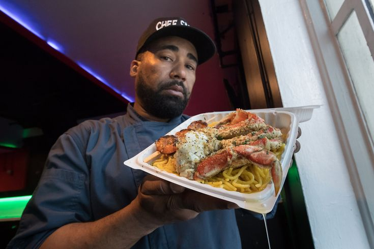 In a cloud of hip-hop music, raucous conversations and cigarette smoke spiraling into the downtown Oakland breeze, 50-some-odd people waited for Edward Wooley to open his one-night-a-week pop-up, Smelly's Creole and Soul Food. The crowd formed a haphazard line, segmented by small clusters of two, three and four people, stretching from the middle of the block at 420 14th St. to the intersection of 14th and Broadway. A few floors above the fray in Complex, downtown Oakland's music venue that…