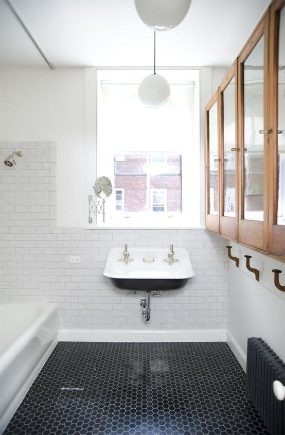Wood cabinets, back hexagonal tile floor and a black & white basin