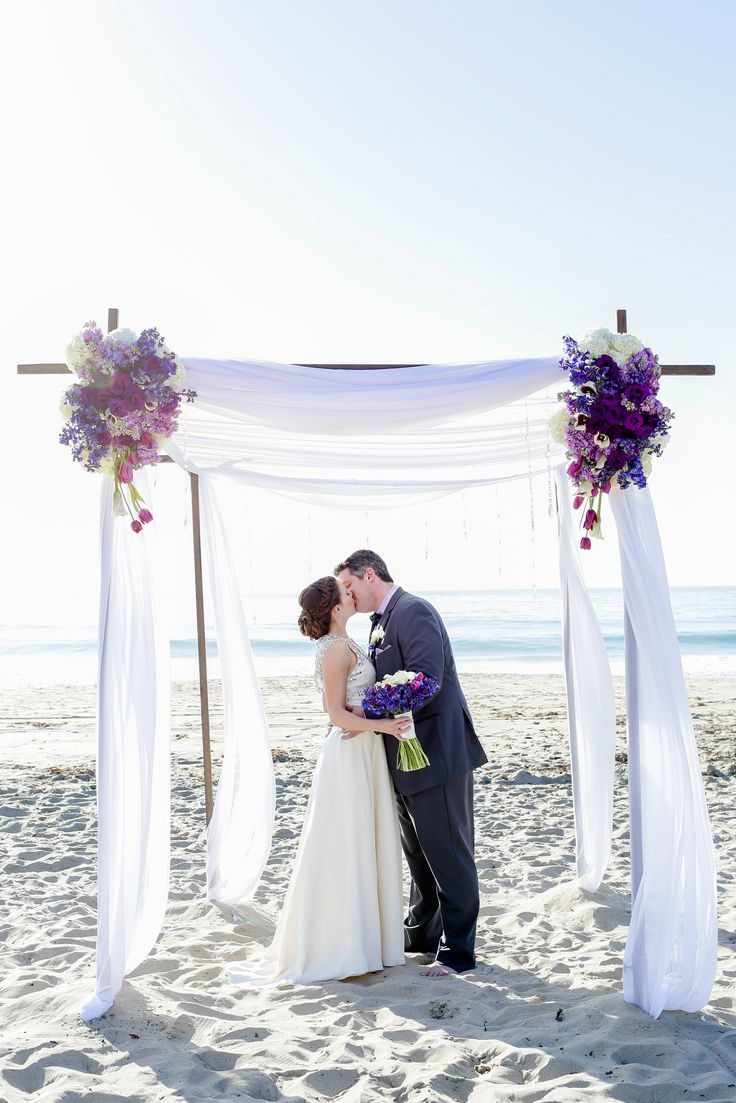 Beach Chic Wedding. Wedding Chuppah. Crystals, purple and blue flowers, tulips, hydrangea, delphinium, calla lilies, wood chuppah with draping fabric. Florals by Jenny//Love with Flare Photography