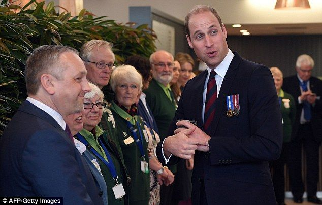 Back in the warm: Britain's Prince William meets staff and volunteers after touring the site's many memorials including the Police Memorial where he laid down a wreath