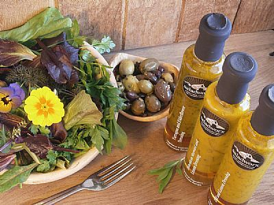a sample of dress me up salad and edible flowers alongside highland premium handmade dressings