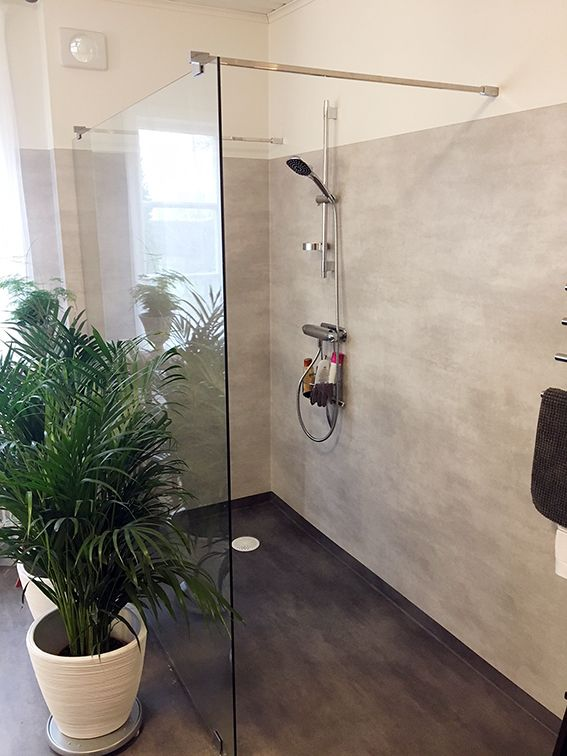 Våtrumsmatta och en fast duschvägg Detta badrum renoverades och en gråmelerad våtrumsmatta valdes här tillsammans med duschväggar från INR