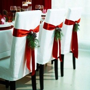 Christmas chairs - red sash on white chair cover with holly and pine cone tucked in. I love this idea