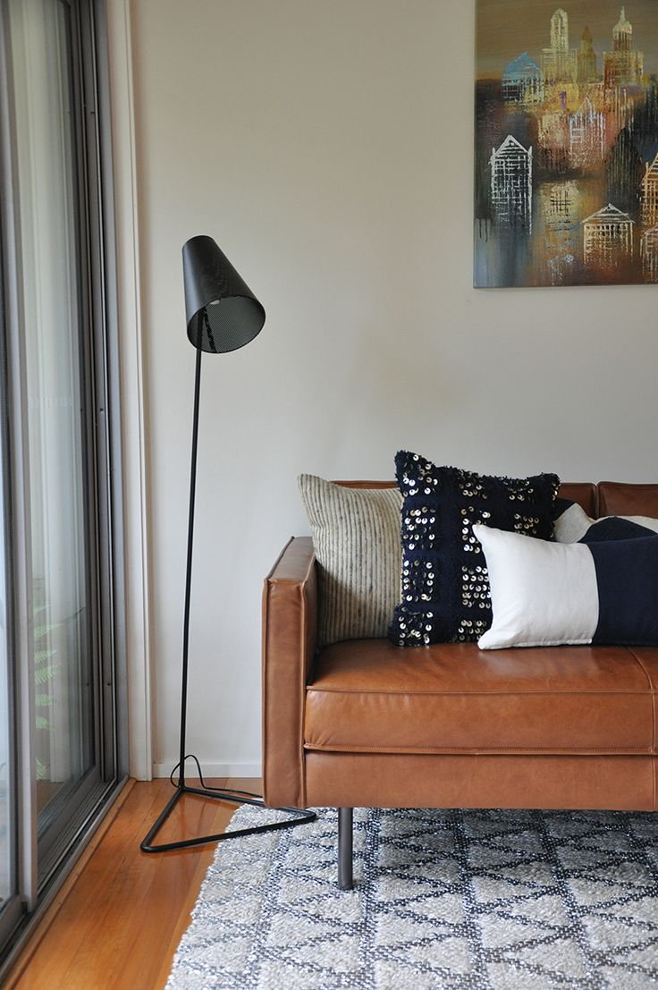 Tan leather sofa with navy cushions