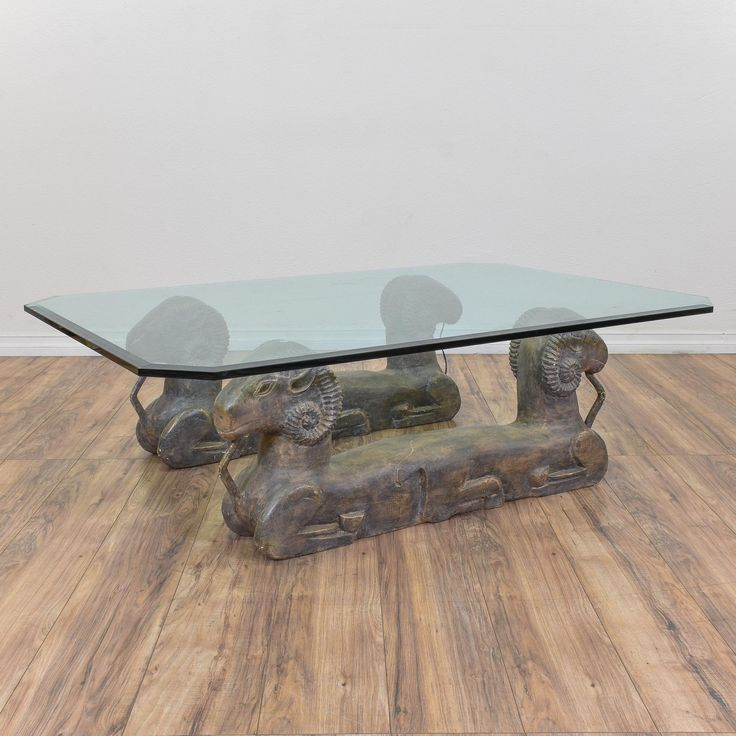 This Egyptian inspired coffee table is featured in a durable metal with an antiqued brass patina finish. This coffee table is in great condition with a glass top, a beveled edge and a unique carved base with 4 ram sphinxes. Eclectic coffee table perfect for adding interest to a space! #eclectic #tables #coffeetable #sandiegovintage #vintagefurniture