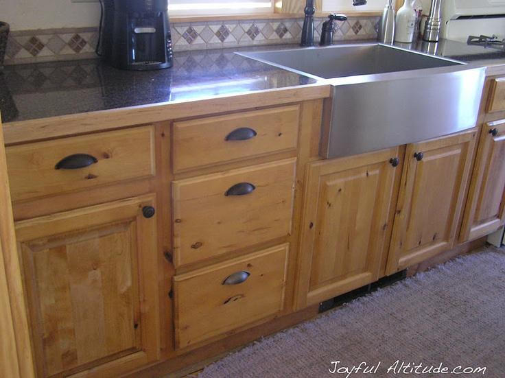 Rustic kitchen, knotty pine kitchen cabinets, stainless steel farmhouse sink. Joyful Attitude via Remodelaholic