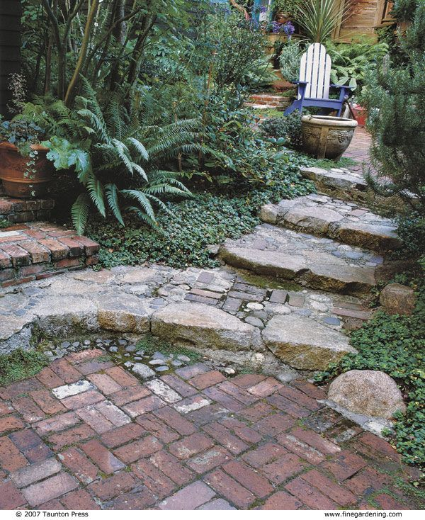 Brick steps line the house and lower courtyard. Grade changes signal you're moving from one place to another. Although the spaces are similar, the narrow passageway divides them -